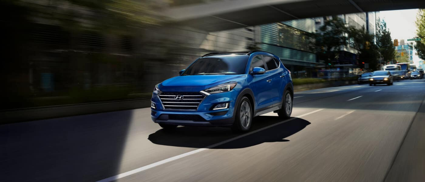 A blue 2020 Hyundai Tucson driving down a city street