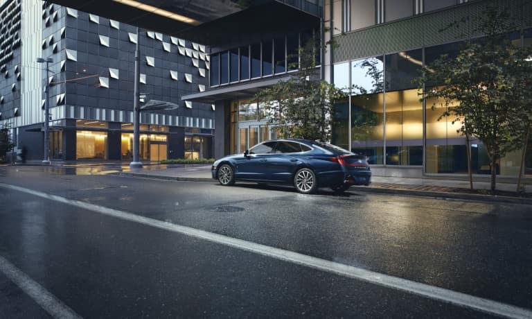 2021 Hyundai Sonata driving down a rainy road