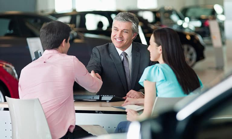Couple making purchase at car dealership