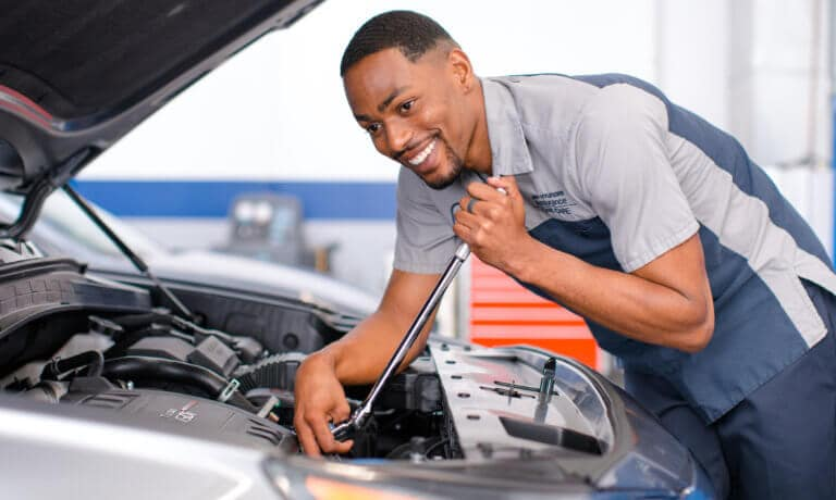 Hyundai service technician looking under hood smiling