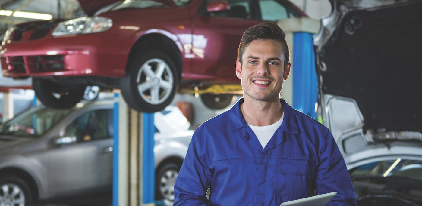 A mechanic standing with an iPad in front of a car